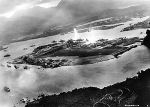 Foto Pearl Harbor dari pesawat terbang Jepang menunjukkan barisan kapal temput di awal penyerangan. Ledakan yang tampak di tengah gambar adalah serangan torpedo ke USS West Virginia